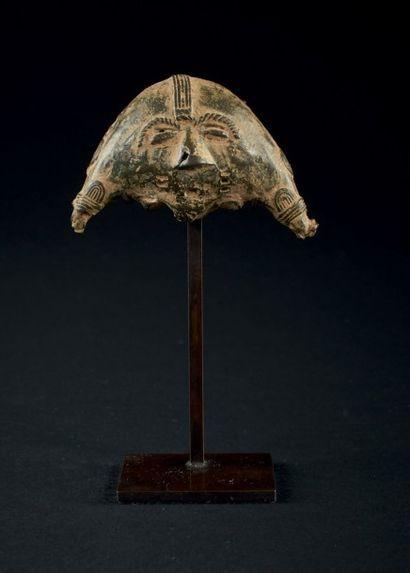 PENDENTIF en forme de demi lune orné d'un visage. Baoulé, Côte d'Ivoire. Bronze....