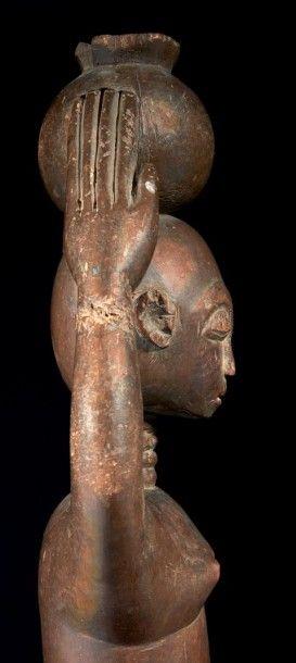 RARE STATUETTE FÉMININE au cou annelé portant une jarre ronde sur sa tête. Les statues...