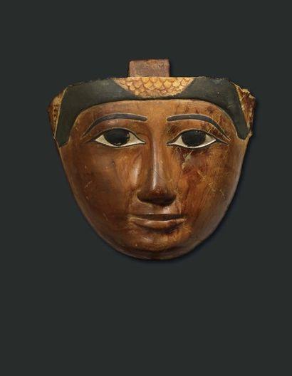 Masque de sarcophage. Il est sculpté, dans un bois dur, du visage de face d'un homme...