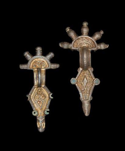 Deux fibules en argent doré avec traces d'émaux....
