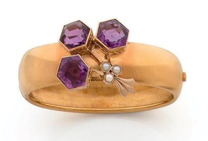 Bracelet jonc plat en or 18K (750) ouvrant, orné de trois pierres violettes dont...