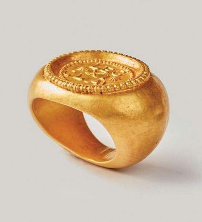 Bague en or. Chaton ovale cerclé de perles...