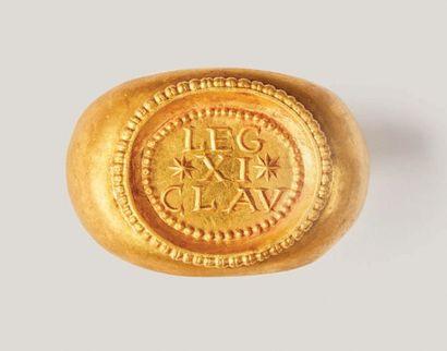 Bague en or. Chaton ovale cerclé de perles portant l'inscription en relief LEG XI...