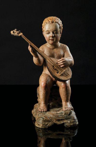 Putto musicien en bois sculpté et polychromé....