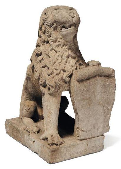 Lion sculpté en pierre bleue tenant un cartouche...