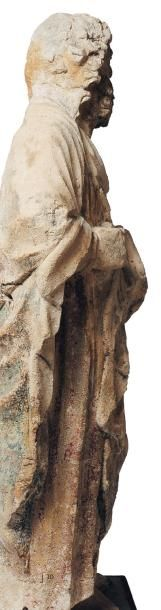Saint en pierre calcaire sculptée. Dos creusé. Debout et pieds nus, il tient un...