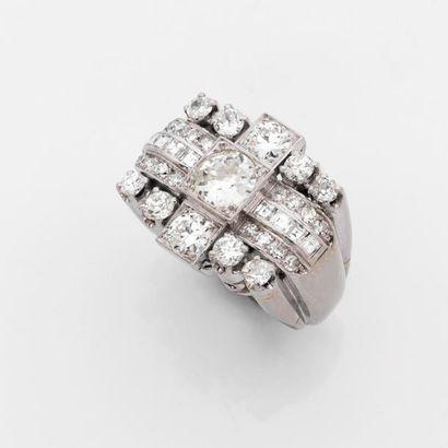 BAGUE chevalière de dame en platine rehaussée d'un diamant brillanté principal encadré...