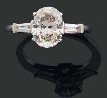 BAGUE ornée d'un diamant ovale monté en solitaire et encadré par deux diamants tapers....