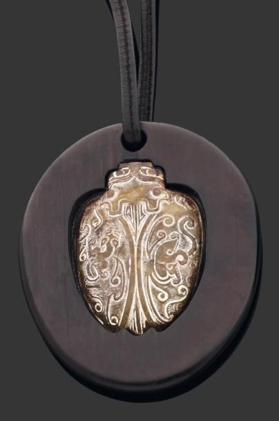 Pendentif en bois d'ébène et jade brun gravé,...
