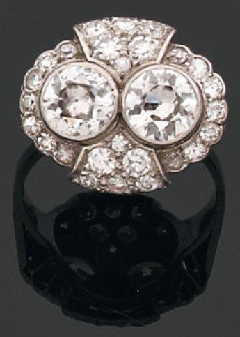 BAGUE de forme ovale ornée de deux diamants brillantés en sertissure sur un pavage...