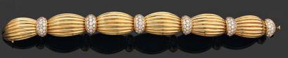 O.J.PERRIN. Années 1980 BRACELET articulé à l'imitation d'un ruban noué en or godronné...