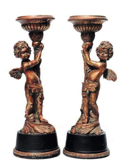 Deux pique-cierges figurant des amours tenant...