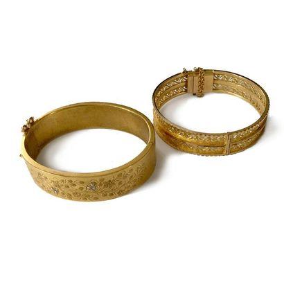 Suite de deux bracelets joncs plats ouvrant en métal doré, l'un ajouré, l'autre...