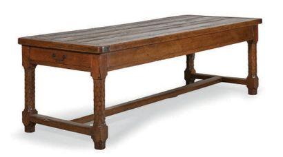 GRANDE TABLE en chêne. Pieds chanfreinés à décor d'écailles reliés par une entretoise...