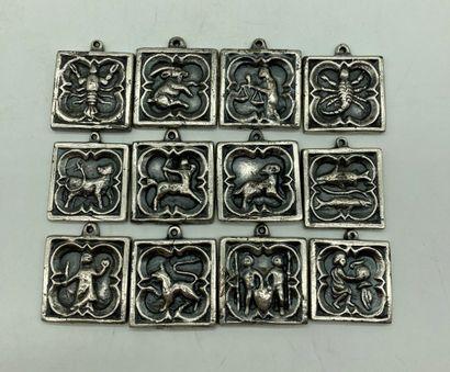 12 MEDAILLONS en métal patiné à décor des...