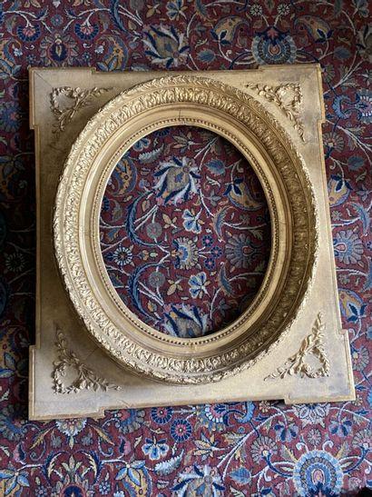 CADRE en bois et stuc doré à vue ovale et écoinçons de branchages fleuris.  XIXème...