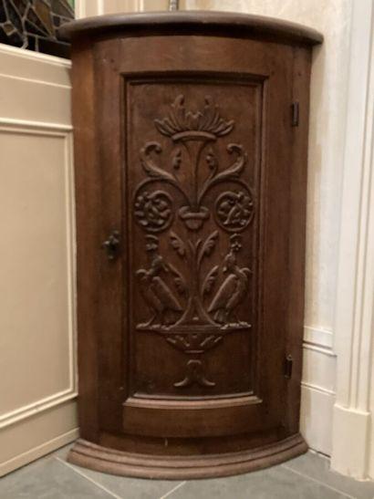 Encoignure en bois naturel ouvrant à une porte à décor sculpté de griffons et rinceaux....