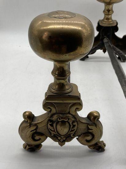 Paire de chenets en bronze et laiton à décor d'enroulements et coquilles.