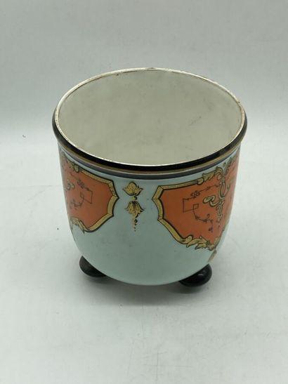 Un cache-pot en porcelaine céladon à décor de médaillons oranges ornés de dorures....