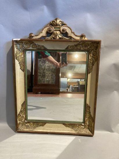 Miroir en bois doré et laqué, à décor d'enroulements....