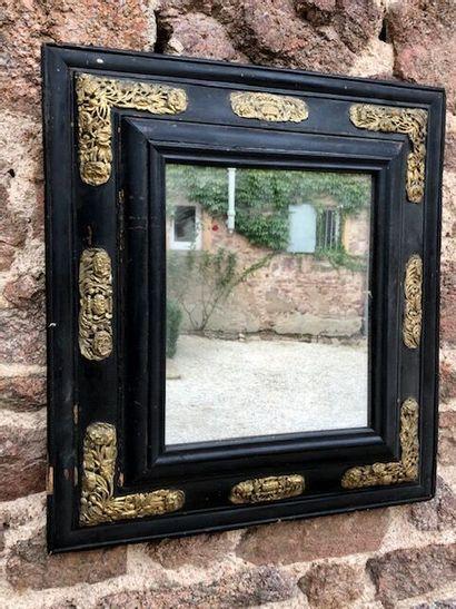 Miroir à profil inversé en bois noirci, encadrement...