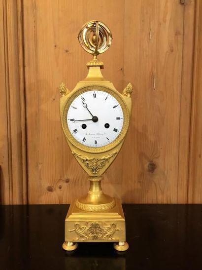 Pendule en bronze ciselé doré en forme d'écusson...