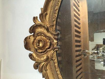 Grand miroir en bois sculpté et redoré, encadrement de baguettes ornées de feuillages,...
