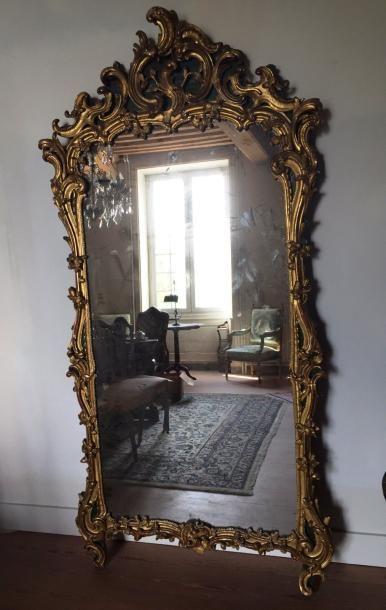 Grand miroir en bois sculpté et redoré, encadrements...