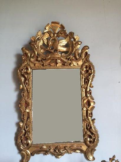 Miroir en bois sculpté et doré, fronton à...