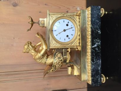 Pendule en bronze doré reposant sur un socle...