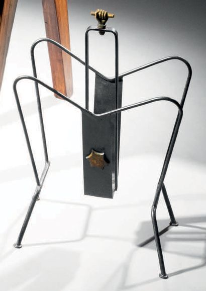 PERRIER & FILS Magazine rack in blackened tubular metal decorated with a brass star...