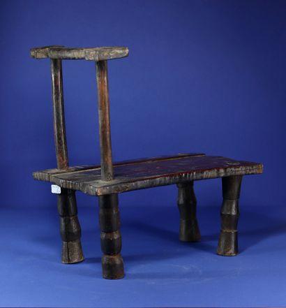 Chaise basse et étroite à belle patine d'usage. Bois et métal. Krou, Côte d'Ivoire....