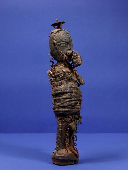 Statue votive en bois représentant un personnage debout, le corps couvert de nombreux...