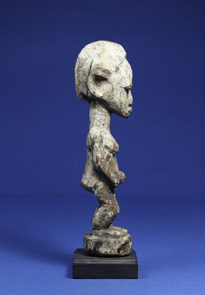 Statuette féminine aux traits schématiques, bois à patine sacrificielle croûteuse...