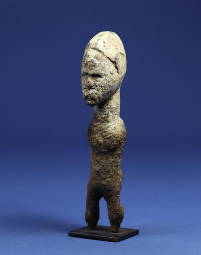 Astonishing macrocephalic statuette, the body disappearing under a crusty material,...
