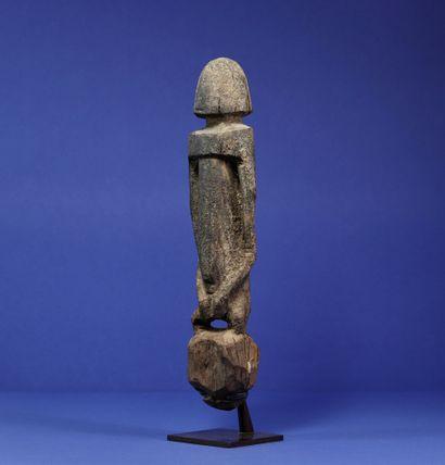 Statue figurant un personnage debout aux traits stylisés, les bras le long du corps,...