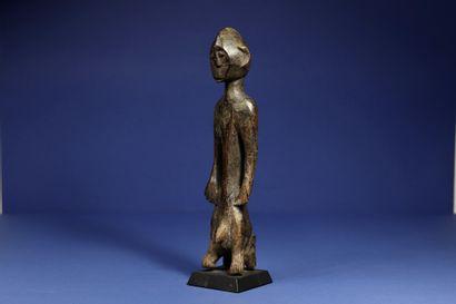 Statuette masculine assise sur un tabouret, les jambes se confondant avec les pieds...