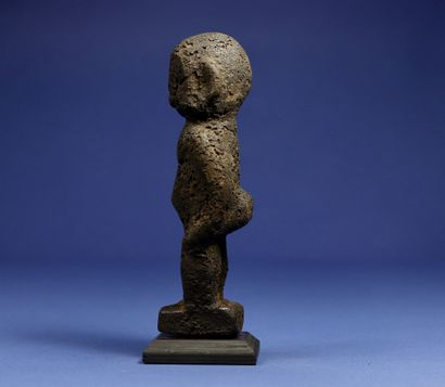 Divination statuette, the details of the sculpture disappearing under a thick black...