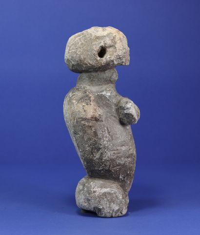 Powerful female anthropomorphic statue, the two hands gripping the chest, the right...
