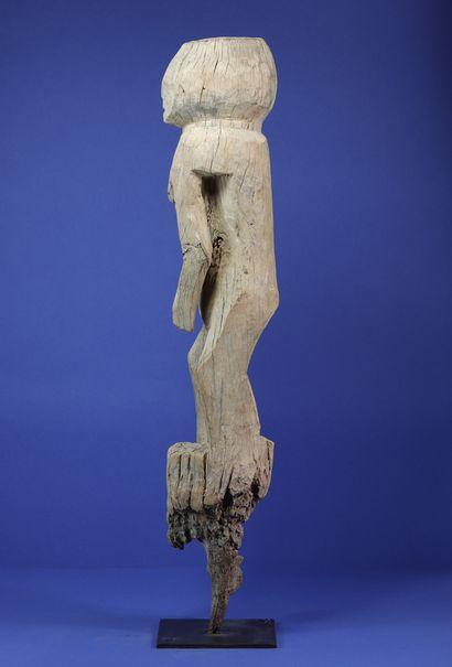 Poteau représentant un personnage féminin debout traité en quelques volumes simples,...