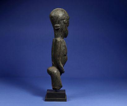 Statue féminine figurée debout, les bras collés au buste, la tête ovoïde. Bois à...