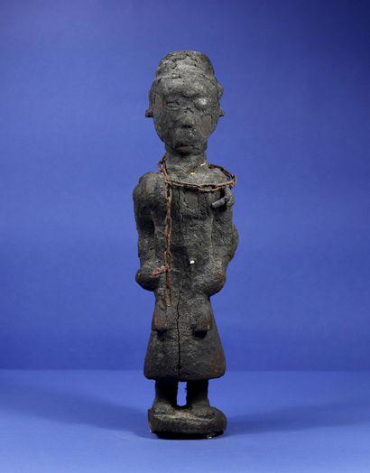 Statue votive en bois représentant un officiant...