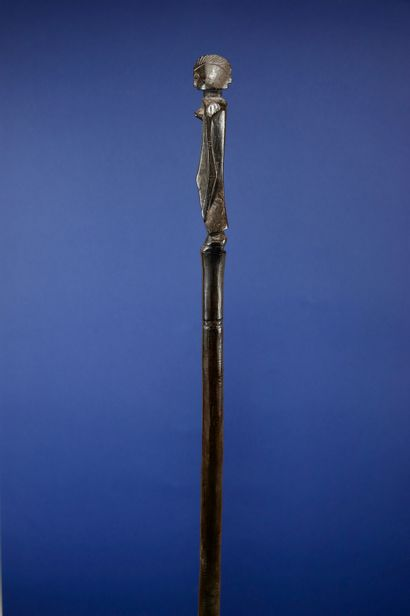 Canne du poro sculptée en son sommet d'un personnage féminin. Bois à profonde patine...
