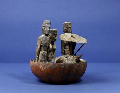 Demi calebasse votive comprenant trois statuettes...