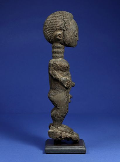 Statue masculine en position debout, entièrement recouverte d'une patine croûteuse,...
