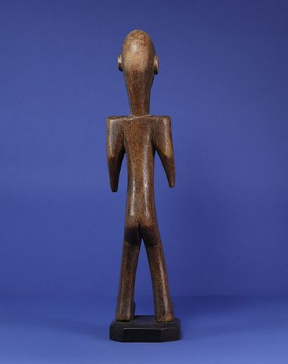 Statue masculine figurant un personnage debout à la silhouette tendue, les épaules...