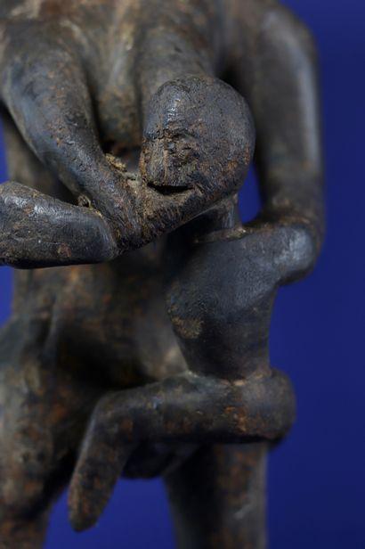Intéressante sculpture figurant une mère allaitant son enfant accroché à un sein,...
