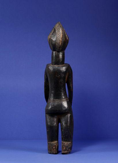 Statue représentant un personnage féminin debout, les épaules et la poitrine projetés...