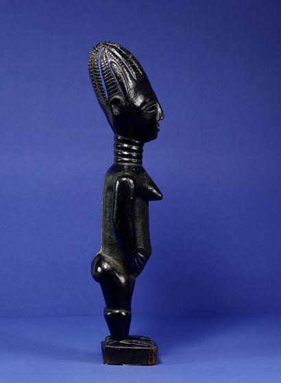 Statue représentant un personnage féminin debout, les bras décollés du corps, les...