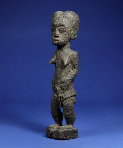 Statue féminine en position debout, entièrement recouverte d'une patine croûteuse,...